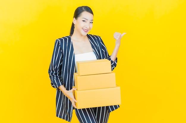 Portret mooie jonge aziatische vrouw met doos klaar voor verzending op kleur achtergrond