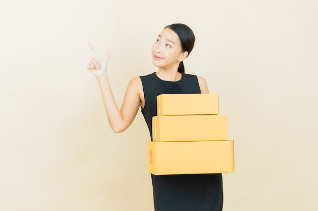 Portret mooie jonge aziatische vrouw met doos klaar voor verzending op kleurenmuur