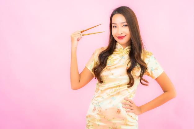 Portret mooie jonge aziatische vrouw met eetstokjes op roze muur