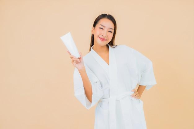 Portret mooie jonge aziatische vrouw met flessenlotion en gezichtsroom op beige
