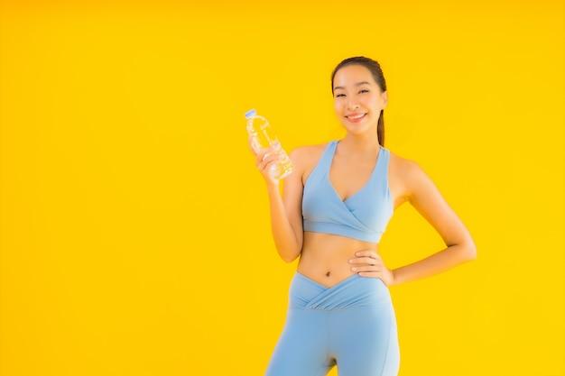 Portret mooie jonge aziatische vrouw met flessenwater op geel