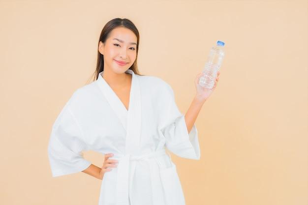 Portret mooie jonge aziatische vrouw met flessenwater voor drank op beige