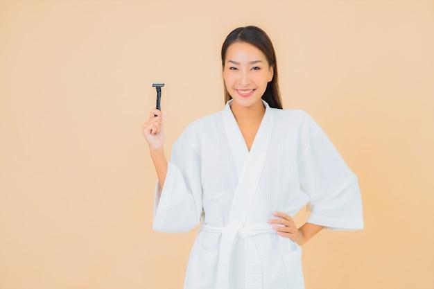 Portret mooie jonge aziatische vrouw met het scheren op beige