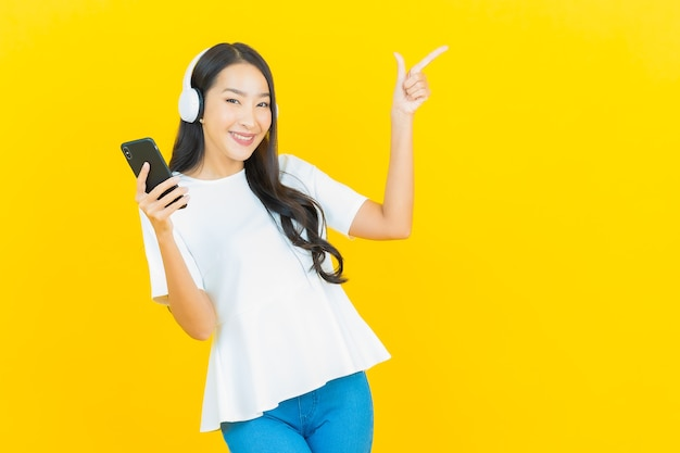Portret mooie jonge aziatische vrouw met hoofdtelefoon en smartphone om muziek op geel te luisteren