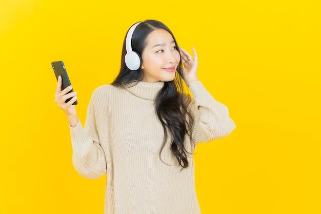 Portret mooie jonge aziatische vrouw met hoofdtelefoon en smartphone om muziek te luisteren op gele achtergrond