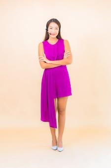 Portret mooie jonge aziatische vrouw met hoofdtelefoon voor call centreerklant op kleurenachtergrond