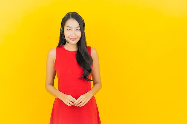 Portret mooie jonge aziatische vrouw met hoofdtelefoon voor communicatie en de dienst van het steuncall centre op gele muur