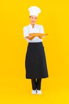 Portret mooie jonge aziatische vrouw met houten snijplank op gele geïsoleerde achtergrond