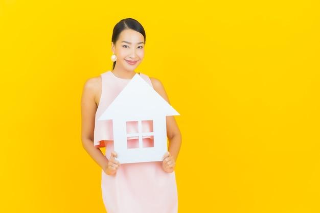 Portret mooie jonge aziatische vrouw met huis of huisdocument ondertekenen op geel