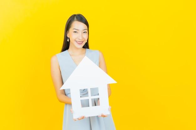 Portret mooie jonge aziatische vrouw met huis of huisdocument teken