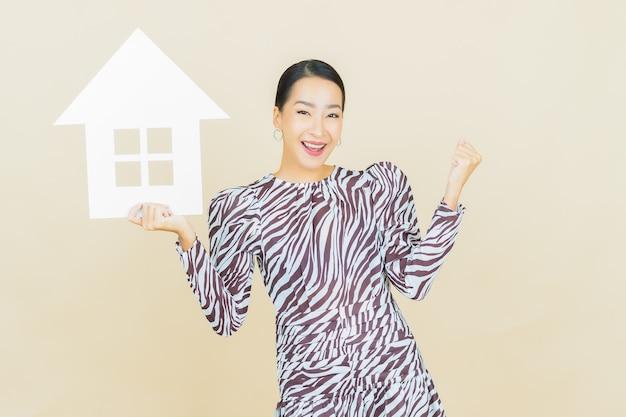 Portret mooie jonge aziatische vrouw met huis of huispapier teken op beige