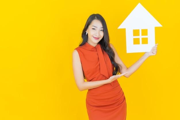 Portret mooie jonge aziatische vrouw met huis of huispapier teken op geel