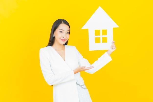 Portret mooie jonge aziatische vrouw met huis of huispapierteken