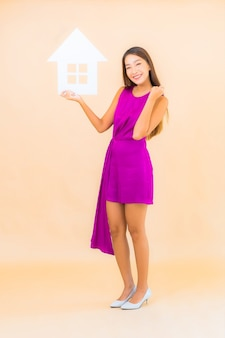 Portret mooie jonge aziatische vrouw met huistekenbord op kleur geïsoleerde achtergrond