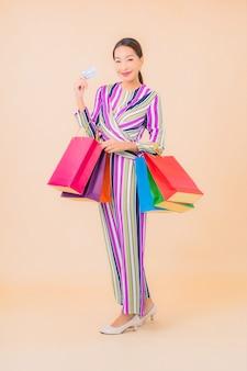 Portret mooie jonge aziatische vrouw met kleurrijke boodschappentas op kleur
