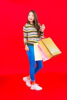 Portret mooie jonge aziatische vrouw met kleurrijke boodschappentas op rode muur