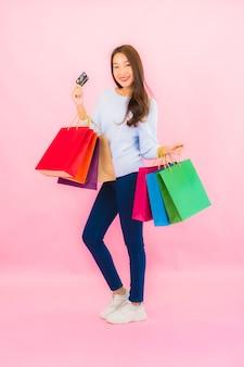 Portret mooie jonge aziatische vrouw met kleurrijke boodschappentas op roze kleur geïsoleerde muur
