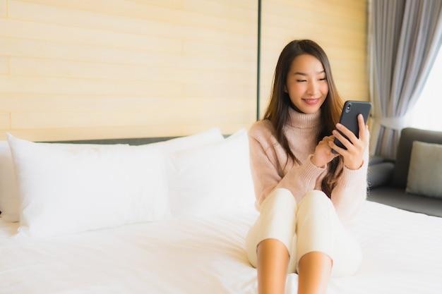 Portret mooie jonge aziatische vrouw met koffiekopje en mobiele telefoon op bed
