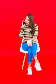 Portret mooie jonge aziatische vrouw met koffiekopje en slimme mobiele telefoon op rode geïsoleerde muur