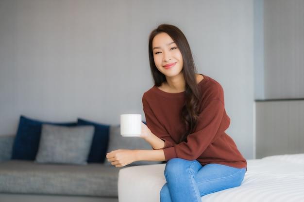 Portret mooie jonge aziatische vrouw met koffiekopje op bed in slaapkamer interieur