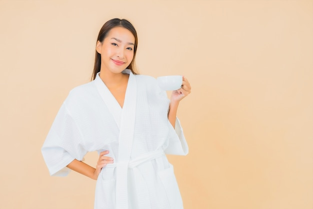 Portret mooie jonge aziatische vrouw met koffiekopje op beige