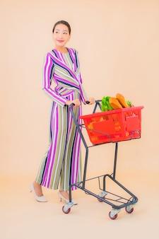 Portret mooie jonge aziatische vrouw met kruidenierswinkelmandje van supermarkt op kleur