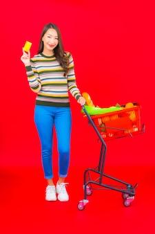 Portret mooie jonge aziatische vrouw met kruidenierswinkelmandje van supermarkt op rode geïsoleerde muur