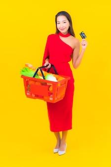 Portret mooie jonge aziatische vrouw met kruidenierswinkelmandje van supermarkt