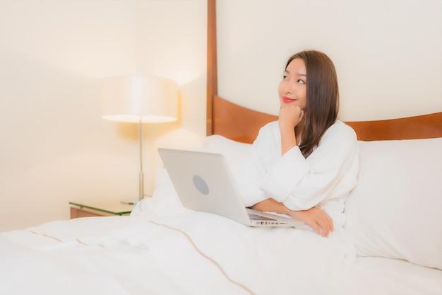 Portret mooie jonge aziatische vrouw met laptop op bed in slaapkamer interieur