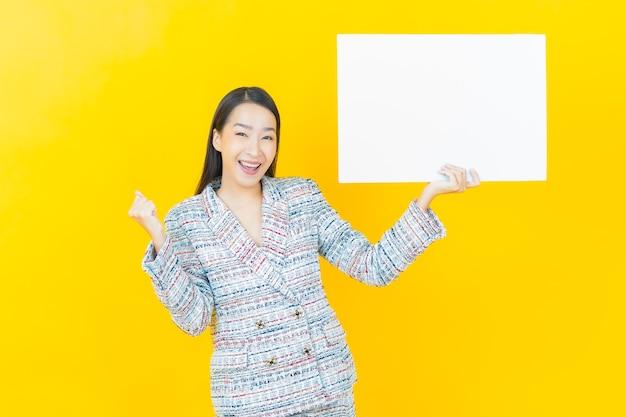 Portret mooie jonge aziatische vrouw met leeg wit reclamebord op kleurenmuur