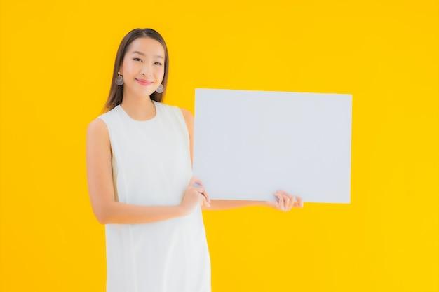 Portret mooie jonge aziatische vrouw met lege witte aanplakbiljet of poster