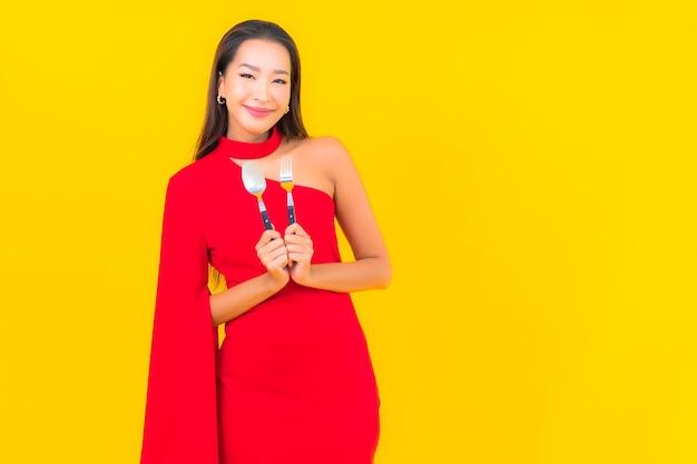 Portret mooie jonge aziatische vrouw met lepel en vork klaar te eten