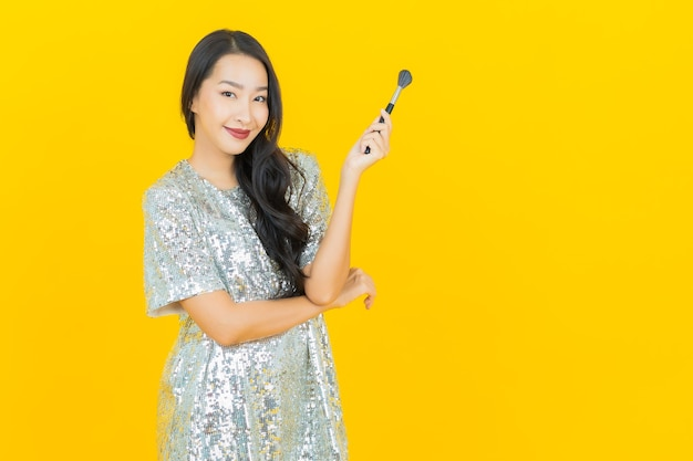 Portret mooie jonge aziatische vrouw met make-up borstel cosmetica op geel