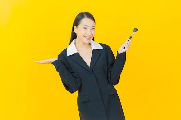 Portret mooie jonge aziatische vrouw met make-up borstel cosmetica op kleur muur