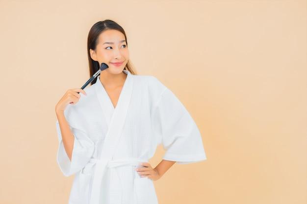 Portret mooie jonge aziatische vrouw met make-upborstel op beige