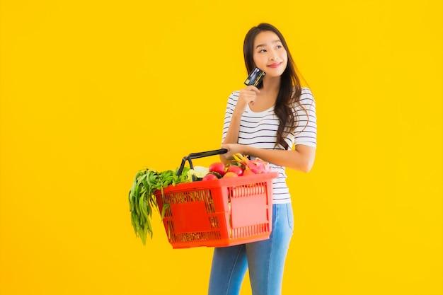 Portret mooie jonge aziatische vrouw met mand kruidenier en kar van supermarkt