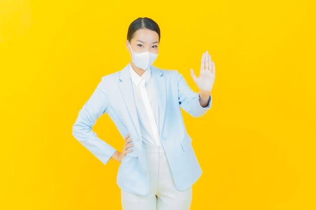 Portret mooie jonge aziatische vrouw met masker om covid19 of virus op geel te beschermen