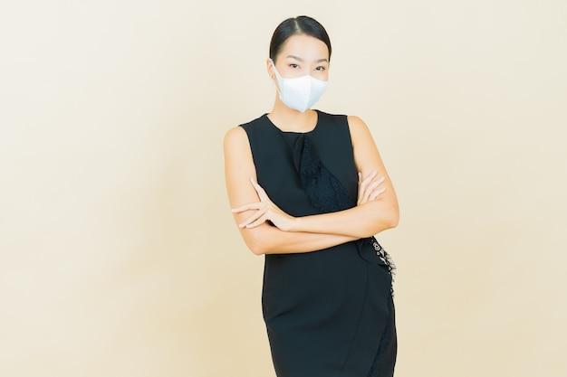 Portret mooie jonge aziatische vrouw met masker om covid19 of virus op gele kleurenmuur te beschermen