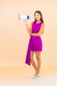 Portret mooie jonge aziatische vrouw met megafoon op kleur geïsoleerde achtergrond