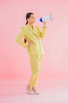 Portret mooie jonge aziatische vrouw met megafoon op kleur