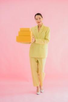 Portret mooie jonge aziatische vrouw met pakketdoos op kleur