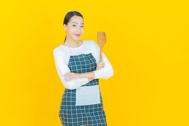 Portret mooie jonge aziatische vrouw met pan en grote lepel op geel