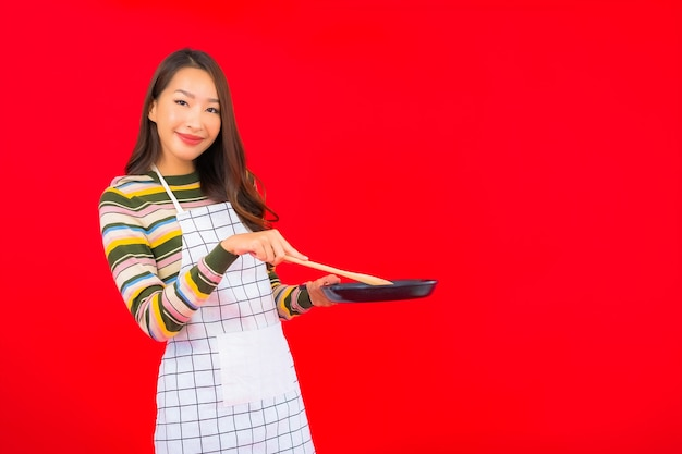 Portret mooie jonge aziatische vrouw met pan klaar om op rode muur te koken