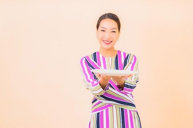 Portret mooie jonge aziatische vrouw met plaat van voedsel op kleur