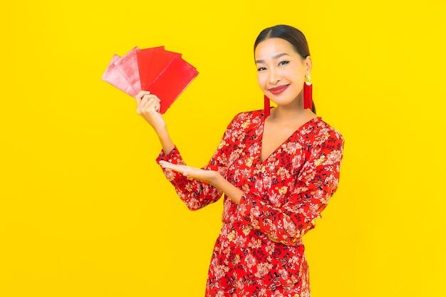 Portret mooie jonge aziatische vrouw met rode enveloppen op gele muur