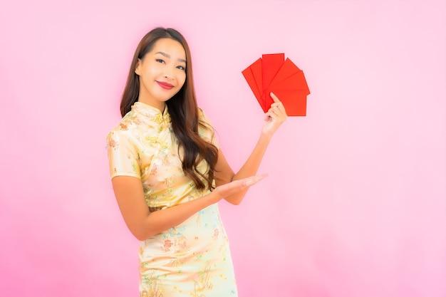 Portret mooie jonge aziatische vrouw met rode enveloppen op roze muur