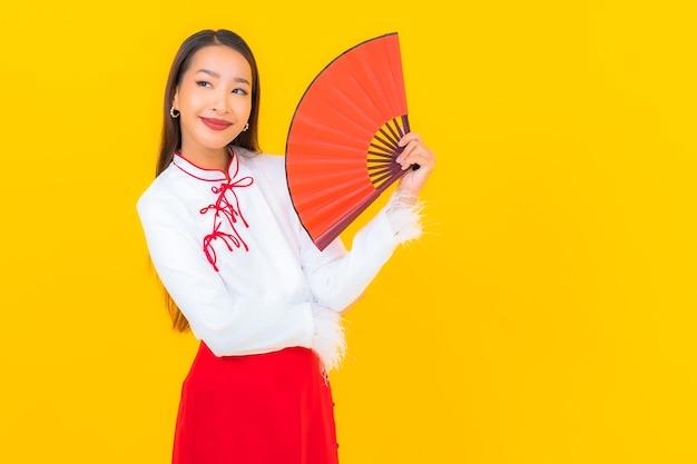 Portret mooie jonge aziatische vrouw met rode enveloppenbrief op geel
