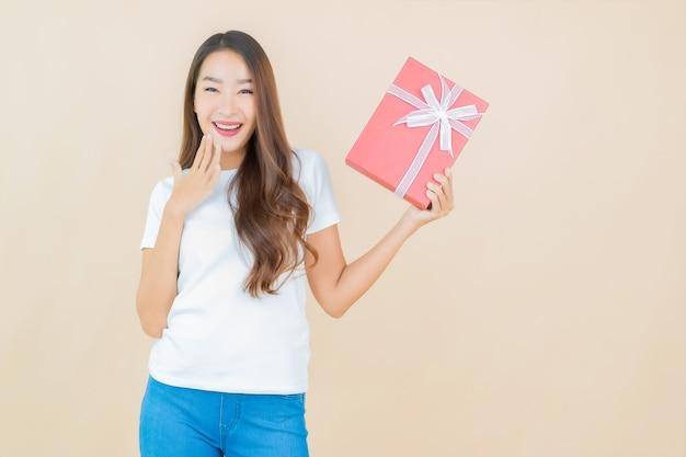 Portret mooie jonge aziatische vrouw met rode geschenkdoos op beige