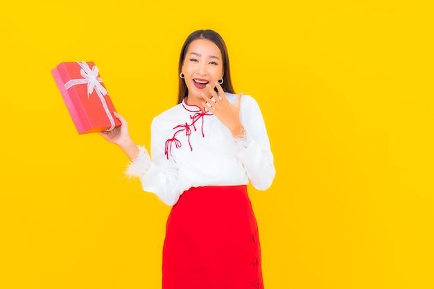 Portret mooie jonge aziatische vrouw met rode geschenkdoos op geel on