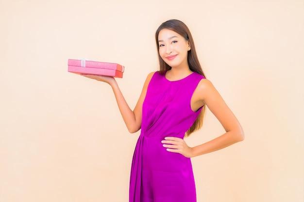 Portret mooie jonge aziatische vrouw met rode geschenkdoos op kleur geïsoleerde achtergrond